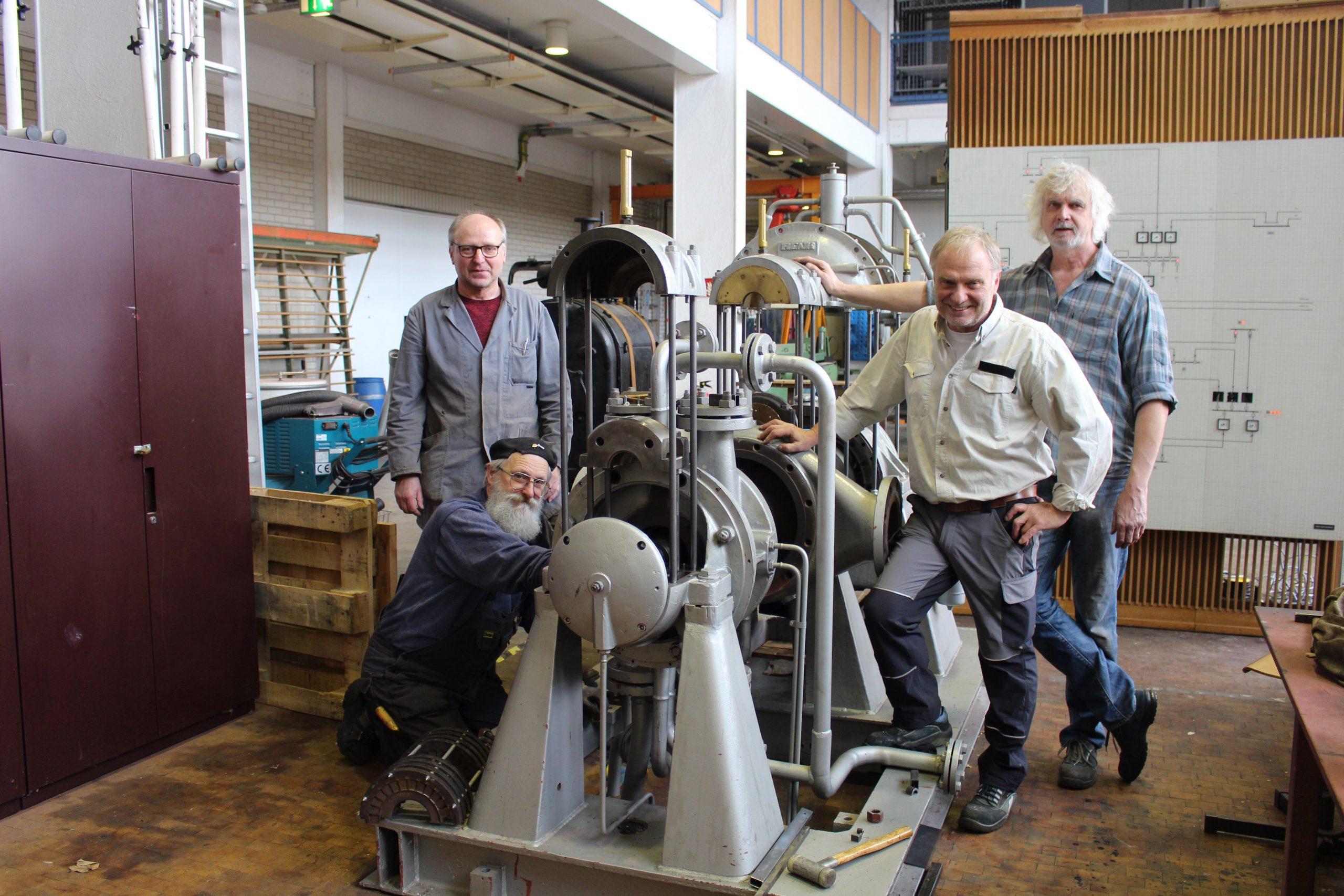 Günther Theis mit den Ehrenamtlichen Peter Maurer, Günter Löser und Hans Schaafhausen vor der Dampfturbine